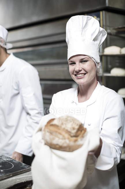 Mujer panadero con pan fresco del horno - foto de stock