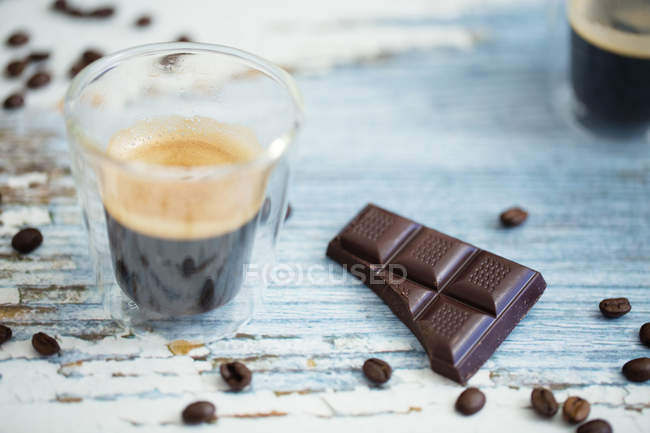Glass cup of espresso, roasted coffee beans and dark chocolate on wood — Stock Photo