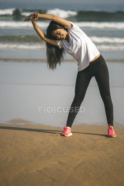 Молодая женщина, растянувшаяся на пляже — стоковое фото