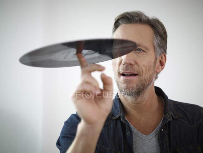 Mature man scrutinizing old vinyl record — Stock Photo