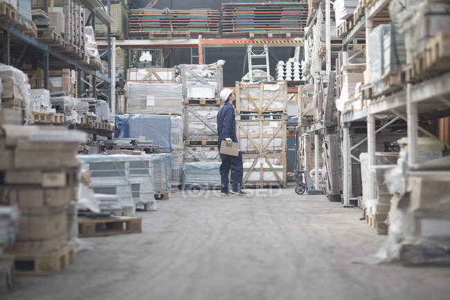 Warehouseman in storehouse looking up — Stock Photo