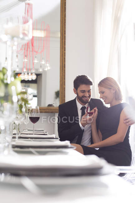 Elegant couple with engagement ring in restaurant — Stock Photo