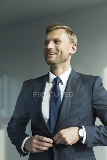 Portrait of smiling Businissman closing jacket — Stock Photo