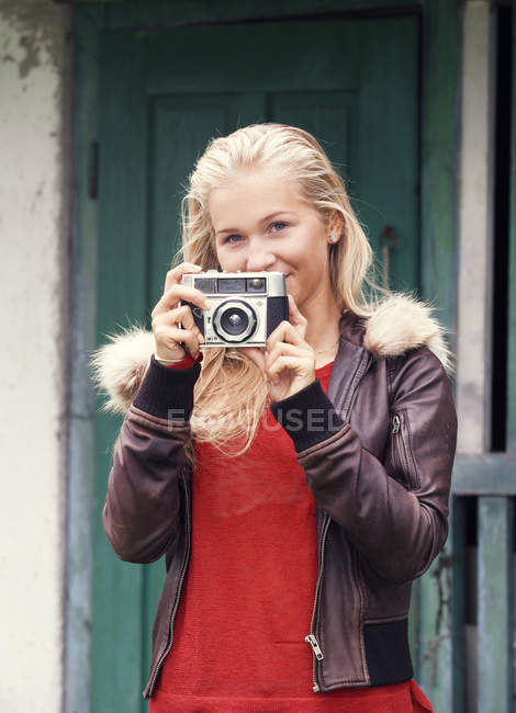 Portrait of smiling teenage girl with old camera — Stock Photo