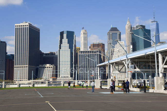 EUA, Nova York, Brooklyn Bridge Park quadras de basquete no cais 2 com arranha-céu Lower Manhattan além . — Fotografia de Stock