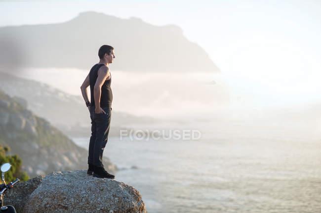 Sud Africa, Città del Capo, motociclista in piedi sulla roccia sulla costa godendo della vista — Foto stock