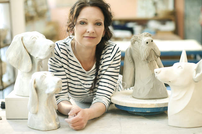 Portrait of potter surrounded by dog figurines — Stock Photo