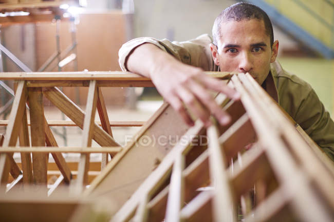 Young Construction worker looking at roof beam design — Stock Photo