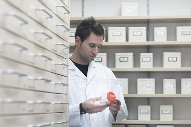 Pharmacist looking at drug bottle in pharmacy store — Stock Photo