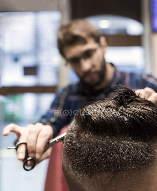 Парикмахер резки молодого человека волосы в парикмахерской — стоковое фото