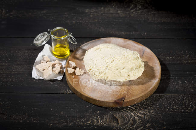 Elevated view of raw pizza dough, yeast and olive oil on dark wood background — Stock Photo
