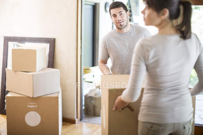 Couple moving house, carrying cardboard boxes — Stock Photo