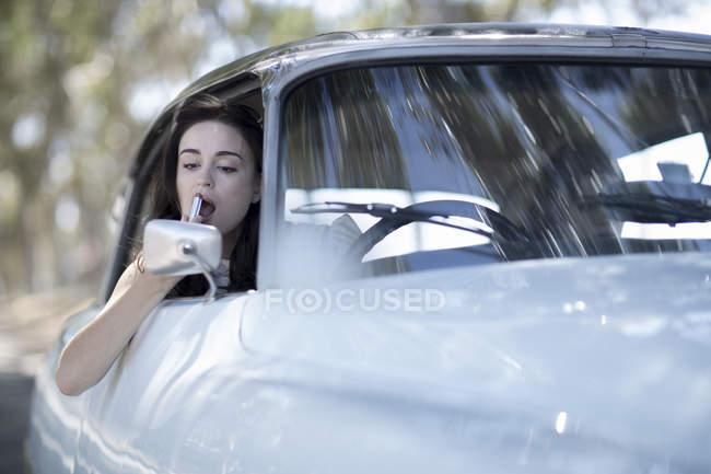 Mujer joven aplicar barra de labios, mirando en el espejo de coche - foto de stock