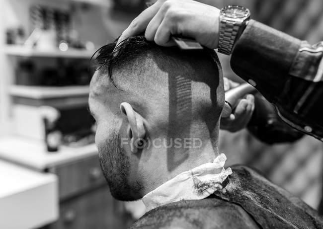 Parrucchiere rasatura testa di giovane in un barbiere — Foto stock