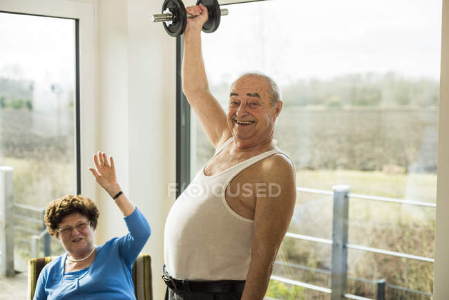 Senior man with dumbbell at home — Stock Photo