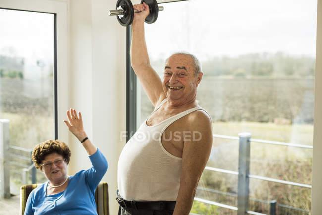 Старший мужчина с гантелями дома — стоковое фото