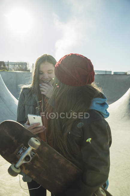 Teenage girls with cell phone in skatepark — Stock Photo