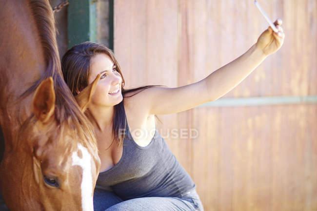 Sonriente niña adolescente toma selfie con caballo en el establo - foto de stock