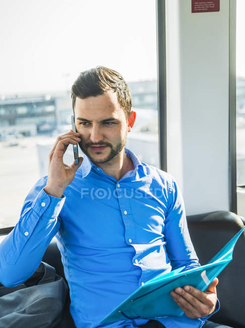 Young businessman on cell phone holding folder — Stock Photo