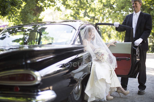 Bride getting out of car before wedding with driver — Stock Photo