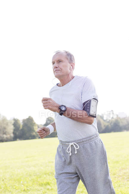 Senior man with earphones jogging in a park — Stock Photo