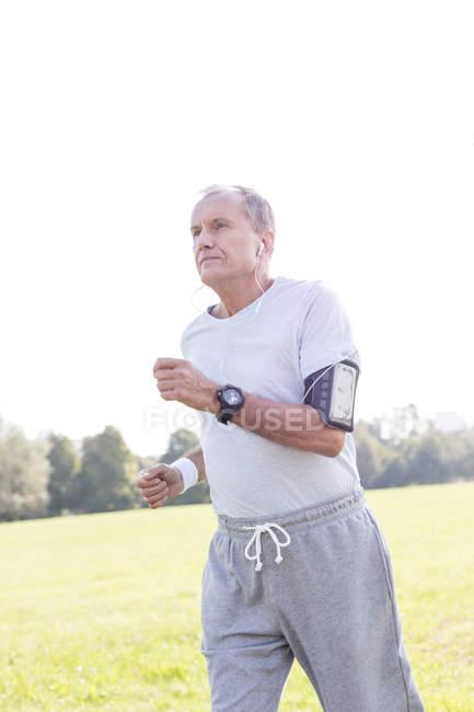 Uomo senior con auricolari jogging in un parco — Foto stock