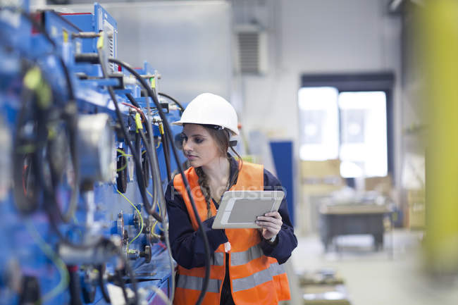 Technician with reflective vest in factory hall inspecting machine with digital tablet — Stock Photo