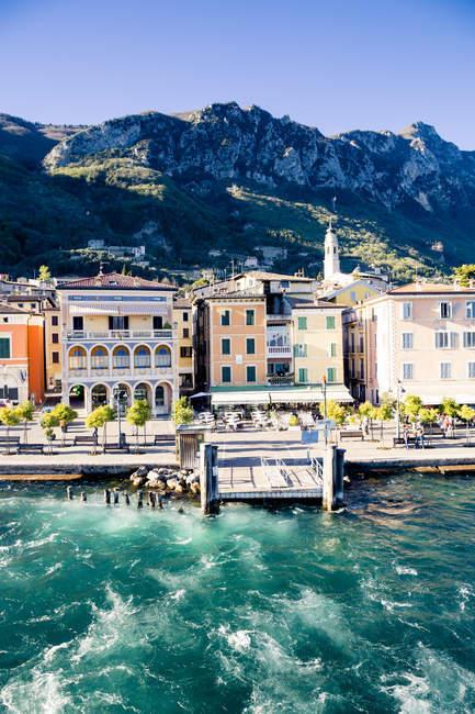 Italia, Lombardía, Provincia de Brescia, Vista a Gargnano, zona de amarre y casas en la costa - foto de stock