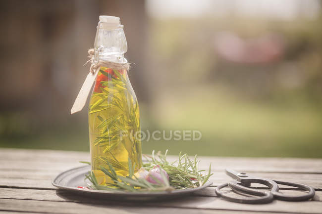 Rosemary oil in bottle, garlic, rosmary on plate, scissors on wood — Stock Photo