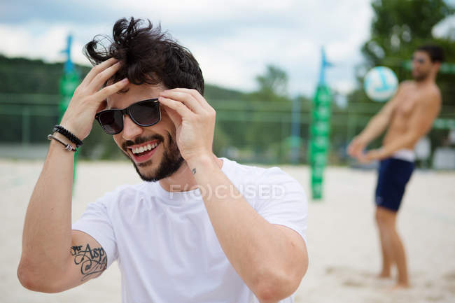 Smiling young man on beach volleyball field — Stock Photo