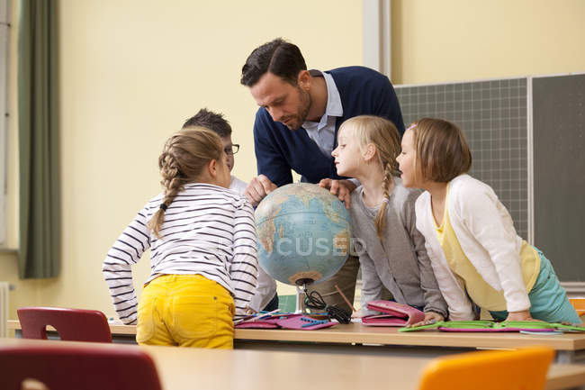 Teacher and pupils looking at globe in classroom — Stock Photo