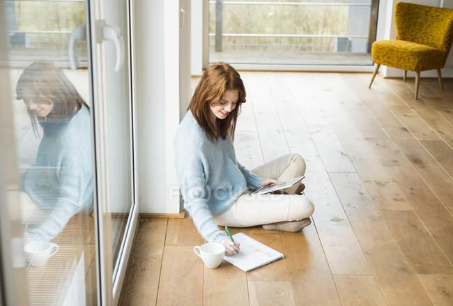 Junge Frau sitzt auf dem Boden und macht sich Notizen — Stockfoto
