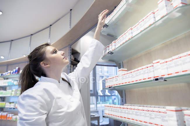 Young pharmacist in pharmacy choosing medication — Stock Photo