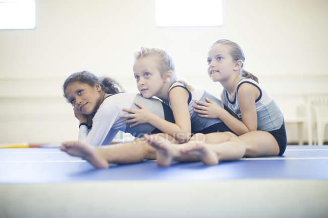 Three girls doing gymnastics exercise on floor — Stock Photo