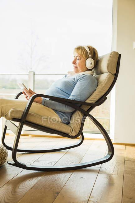 Mulher idosa em casa com fones de ouvido e tablet digital — Fotografia de Stock