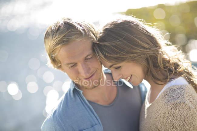 Улыбающаяся молодая пара на берегу озера — стоковое фото
