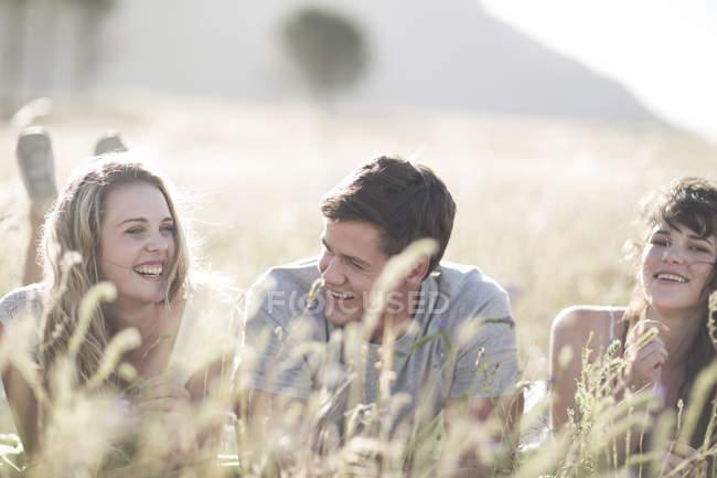 South Africa, Friends lying in field, having fun — Stock Photo