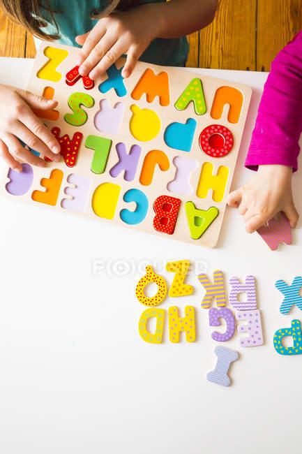 Manos de las niñas con rompecabezas de alfabeto de madera - foto de stock
