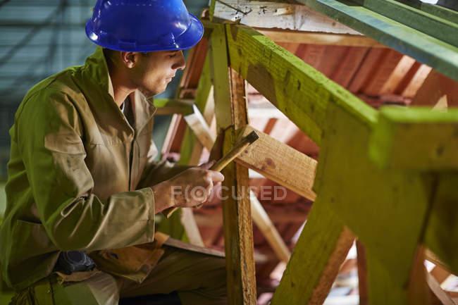 Giovane operaio di costruzione lavorando su travi del tetto — Foto stock