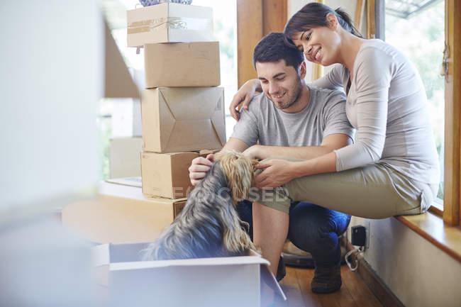 Casal movendo casa compartilhando um momento com o cão — Fotografia de Stock