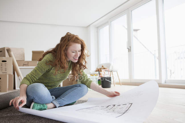 Young woman in new flat with cardboard boxes looking at ground plan — Stock Photo