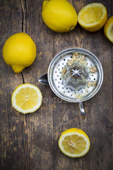 Lemon squeezer and organic lemons on table — Stock Photo