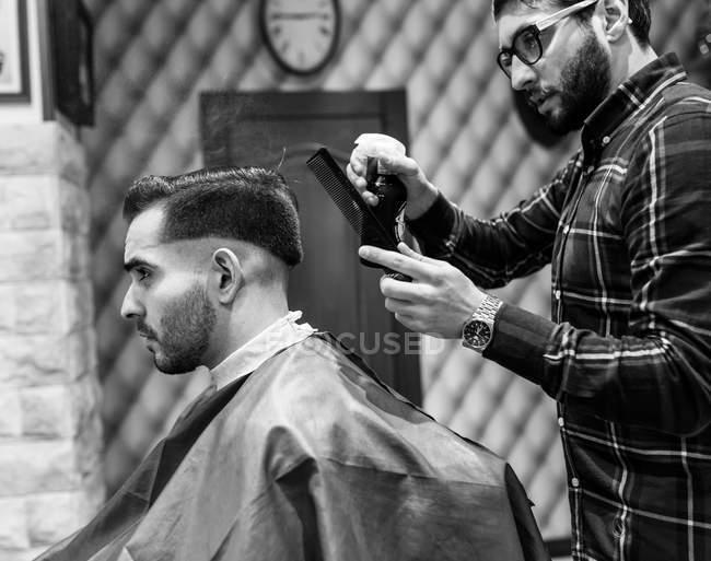 Парикмахер и клиент в парикмахерской — стоковое фото
