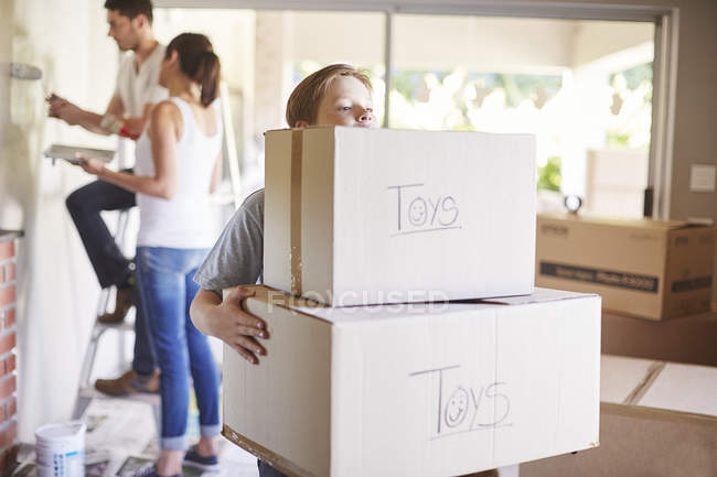 Family moving house, boy carrying boxes — Stock Photo
