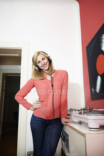Smiling young woman with headphones and record player at home — Stock Photo
