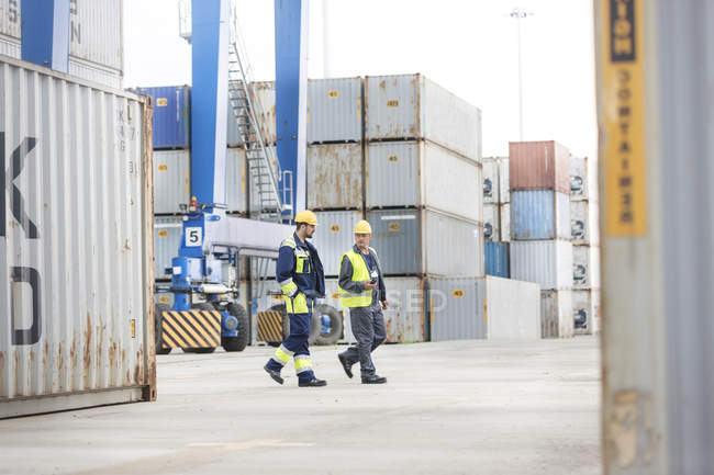 Two men wearing protective clothing walking at container port — Stock Photo