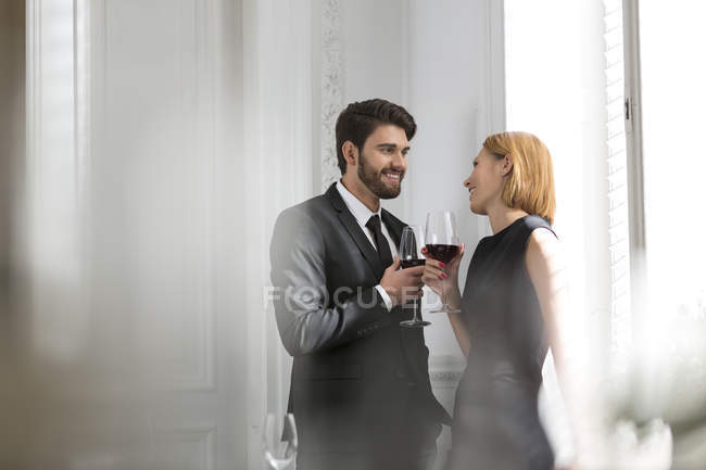 Elegant couple with red wine glasses in restaurant — Stock Photo