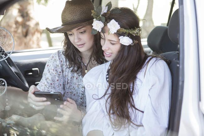 Друзья в дороге смотрят на мобильный телефон — стоковое фото