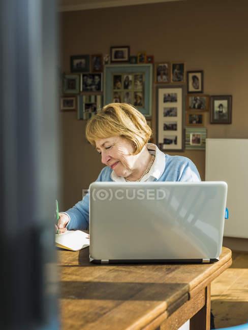 Seniorin zu Hause mit Laptop und Notizbuch — Stockfoto
