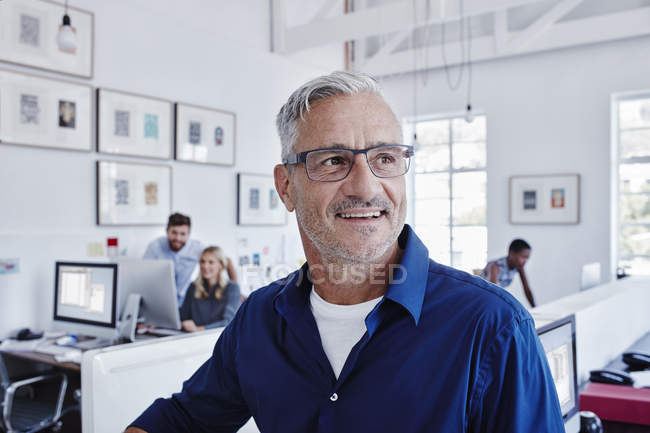 Smiling businessman in office with staff in background — Stock Photo